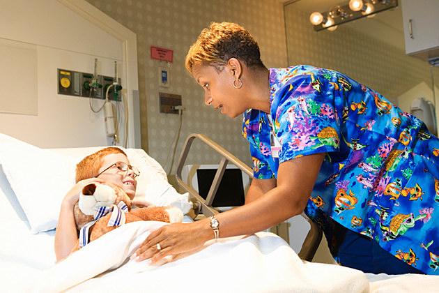 Nurse helping boy in hospital bed